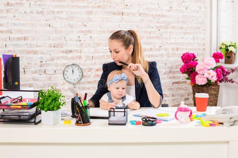 Mamã e mulher de negócios que trabalham com computador portátil em casa e que jogam com seu bebé foto de stock