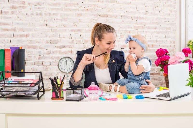Mamã e mulher de negócios que trabalham com computador portátil em casa e que jogam com seu bebé fotografia de stock royalty free