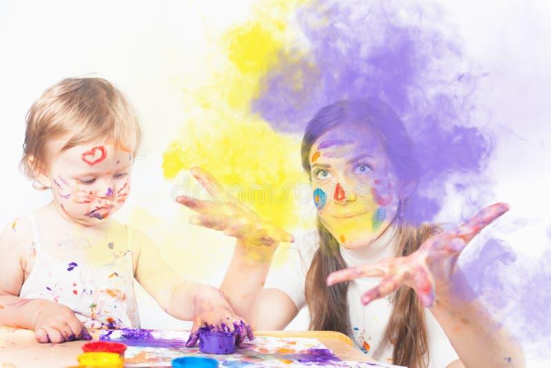 A mamã e o bebê tiram com tintas coloridas imagens de stock