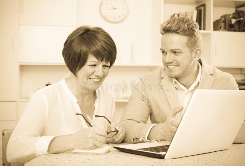 A mamã e o filho contentes consideram o software no portátil fotografia de stock royalty free