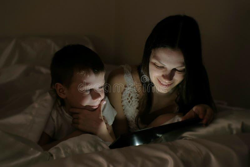 A mamã e o filho escolhem o que olhar antes de ir para a cama na tabuleta sob a cobertura fotografia de stock royalty free