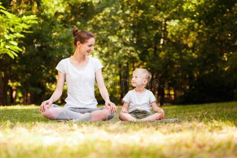 A mamã e o filho estão praticando a ioga no parque fotos de stock royalty free