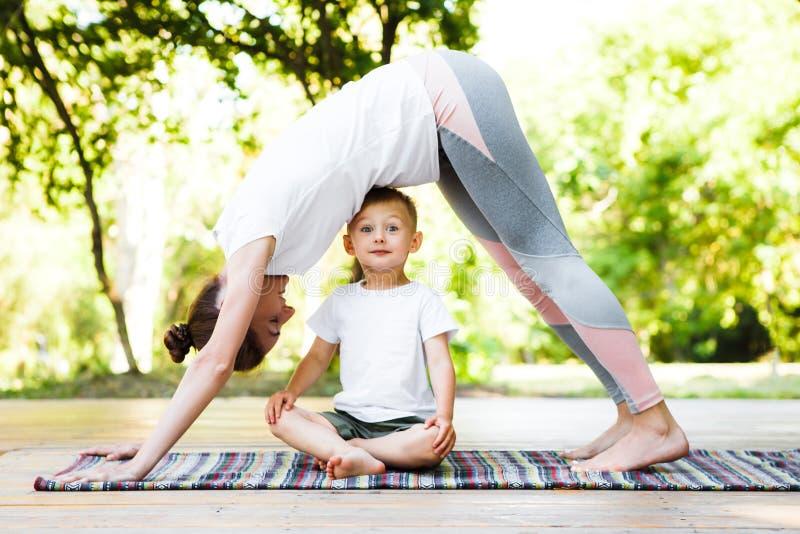 A mamã e o filho estão praticando a ioga no parque imagem de stock royalty free
