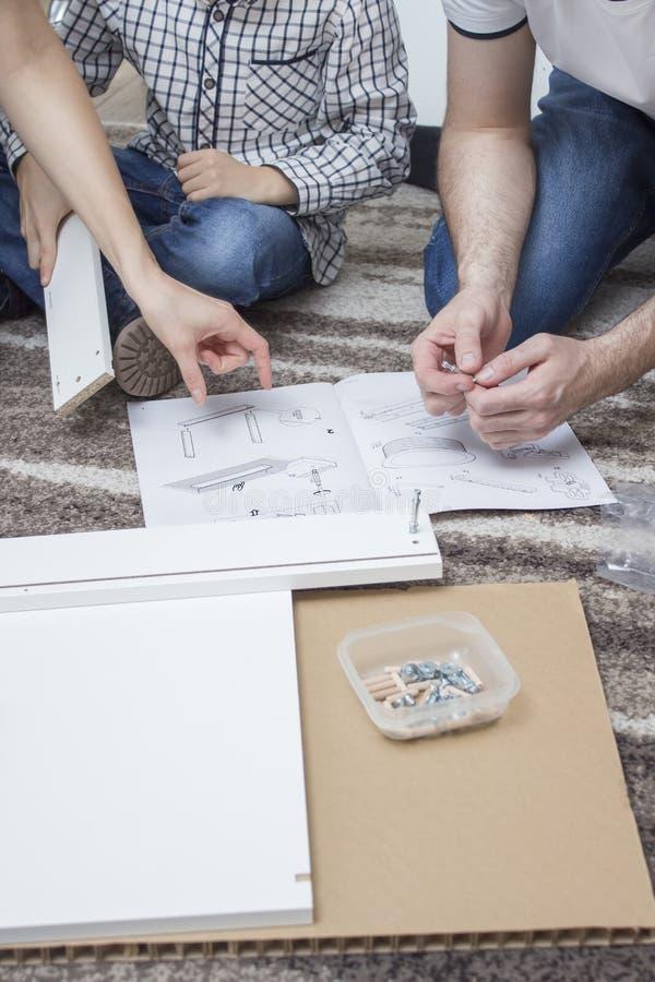 A mamã e o filho gastam sua própria mobília Sentam-se no tapete e comparam-se a parte de mobília com a ilustração no asse fotografia de stock royalty free