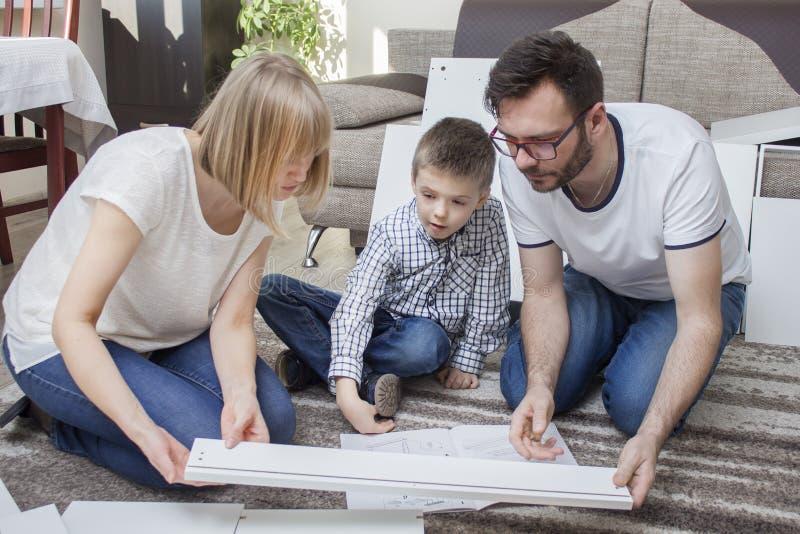 A mamã e o filho gastam sua própria mobília Sentam-se no tapete e comparam-se a parte de mobília com a ilustração no asse imagens de stock