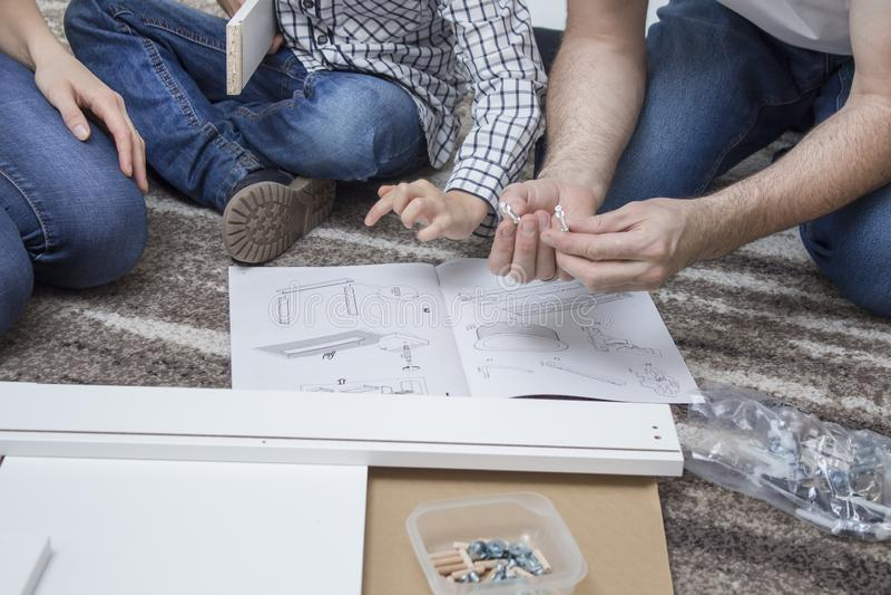 A mamã e o filho gastam sua própria mobília Sentam-se no tapete e comparam-se a parte de mobília com a ilustração no asse imagem de stock