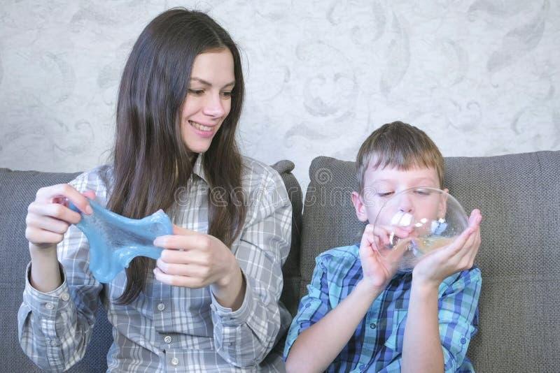 A mamã e o filho inflam bolhas grandes do limos Jogo com limo imagens de stock royalty free
