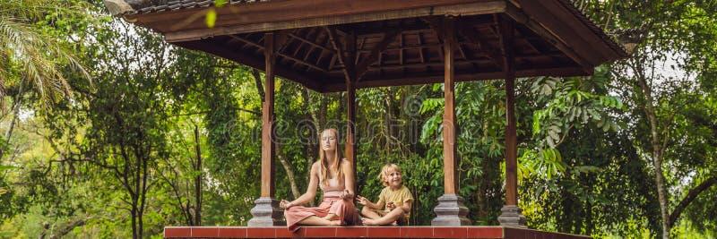 A mamã e o filho meditam a ioga praticando na BANDEIRA tradicional do miradouro do balinesse, formato longo foto de stock royalty free