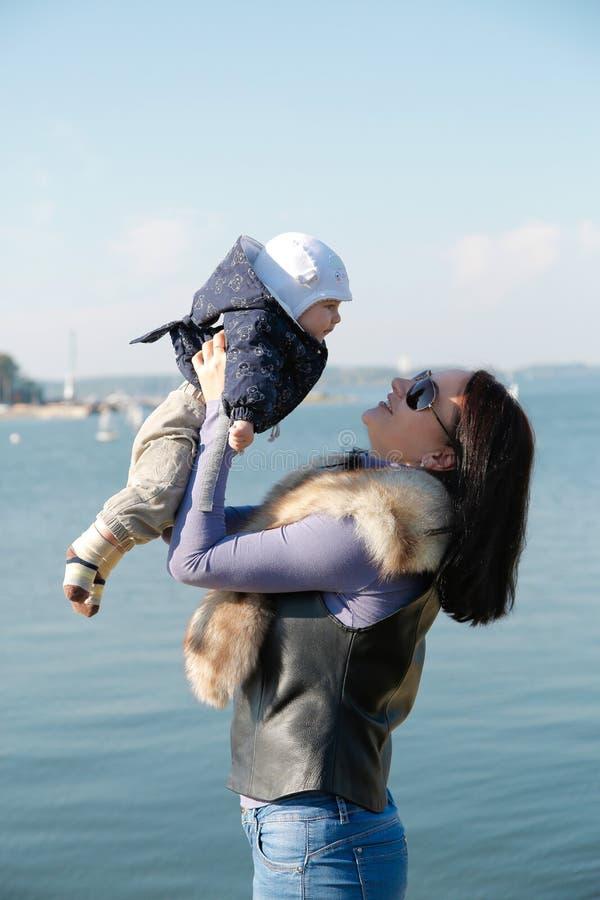 A mamã e o filho têm o divertimento na costa do mar azul fotografia de stock