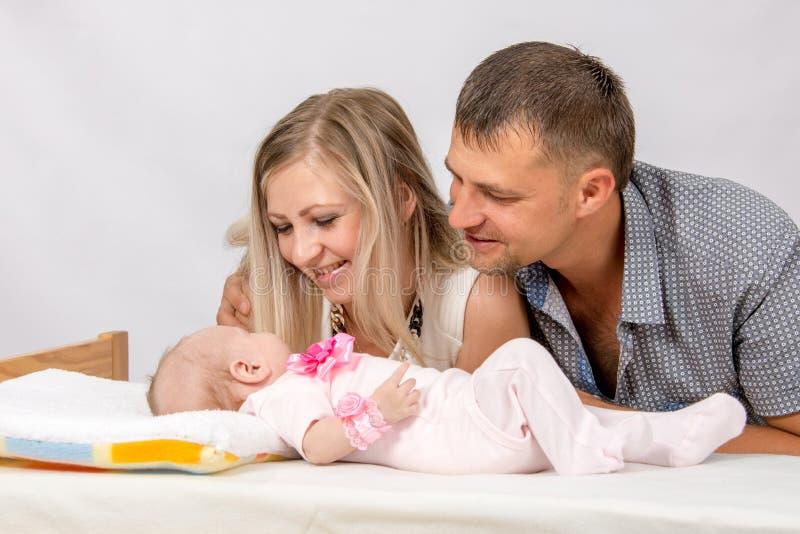 A mamã e o paizinho felizes olham seu bebê de dois meses imagens de stock