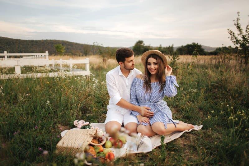 A mamã e o paizinho futuros sentam-se no campo A mulher gravida com seu marido pôs suas mãos sobre a barriga imagens de stock royalty free