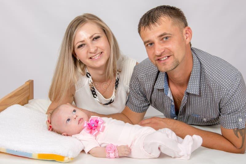 A mamã e o paizinho que olham o quadro são próximos a um bebê de dois meses imagens de stock