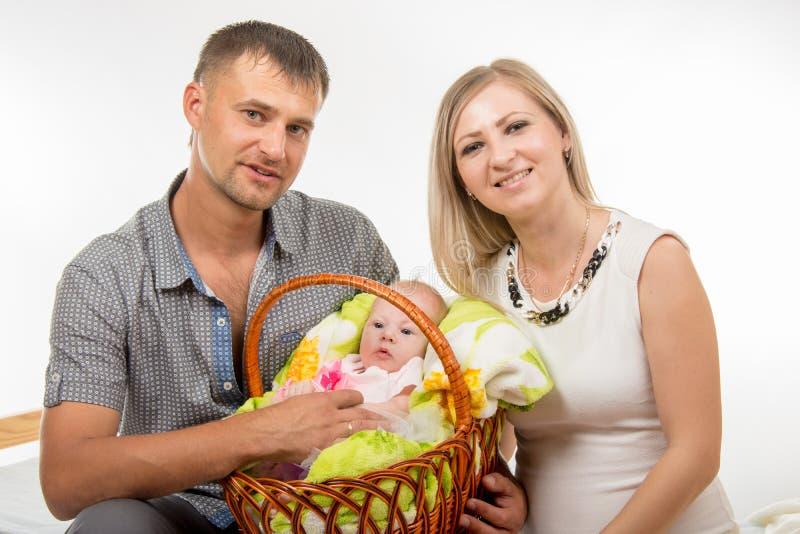 A mamã e o paizinho sentam-se na cama e em guardar um bebê de dois meses em uma cesta fotografia de stock royalty free