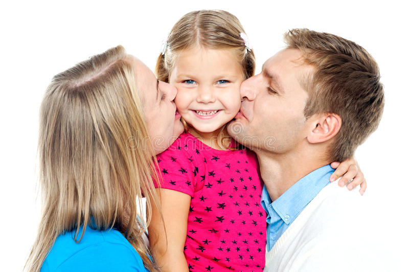 Mamã e paizinho que beijam seu miúdo bonito foto de stock