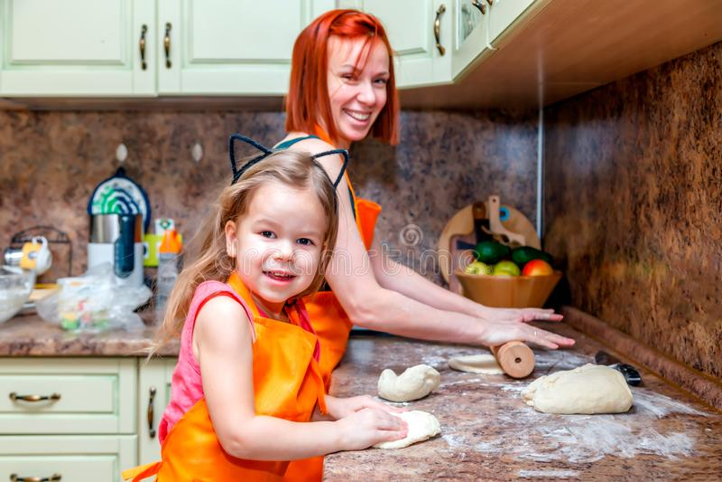 A mamã e pouca menina bonito nos aventais alaranjados, sorrindo e fazendo a pizza caseiro, rolam a massa em casa na cozinha Conce fotos de stock