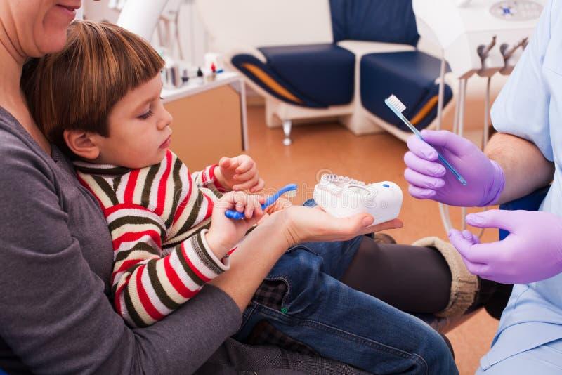 Mamã e seu filho pequeno que visitam o dentista imagem de stock