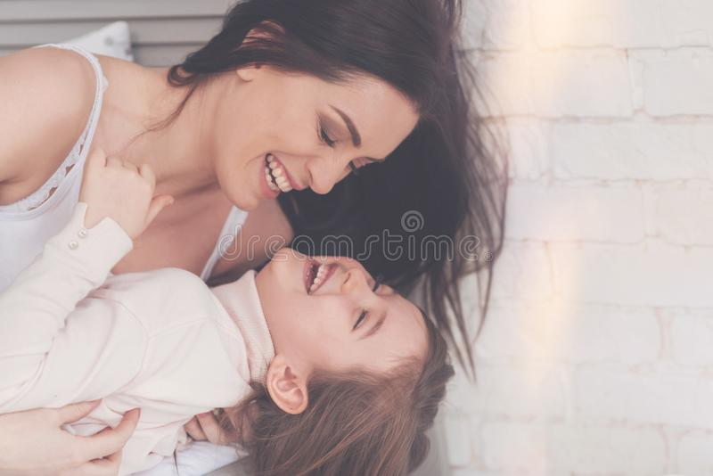 Mamã e sua criança que compartilham de um bom riso fotografia de stock