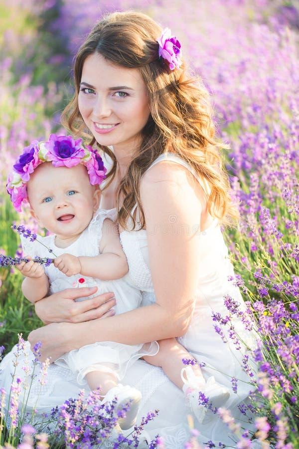 A mamã e sua filha em uma alfazema colocam fotografia de stock
