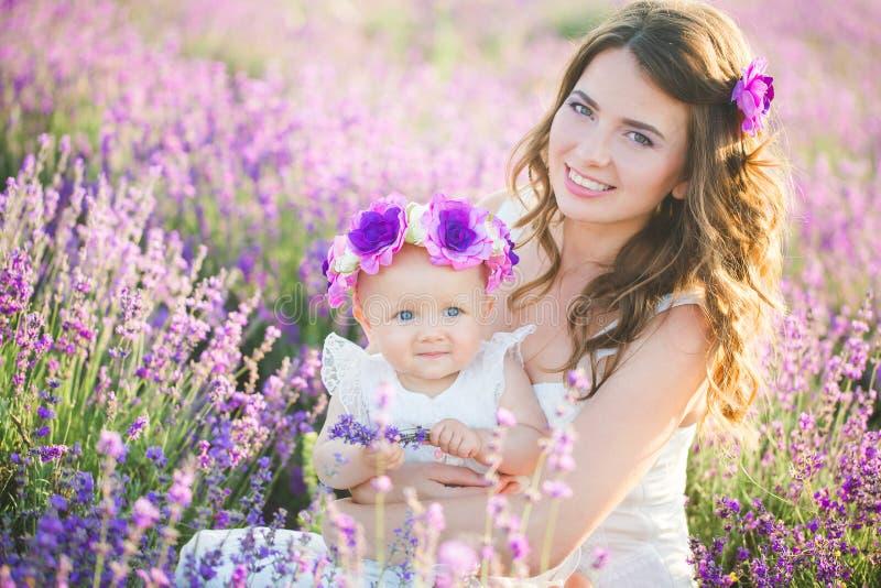 A mamã e sua filha em uma alfazema colocam imagens de stock