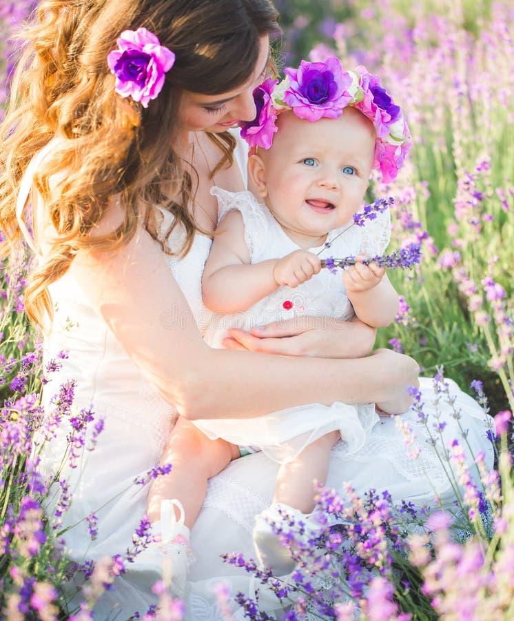 A mamã e sua filha em uma alfazema colocam foto de stock