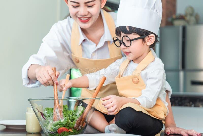 A mamã e sua filha pequena que cozinham o molho bolonhês para a salada na cozinha, lá são vapor que escapa da bandeja no coziment imagem de stock