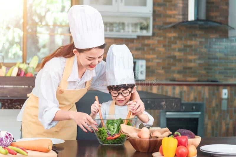 A mamã e sua filha pequena que cozinham o molho bolonhês para a salada na cozinha, lá são vapor que escapa da bandeja no coziment fotografia de stock