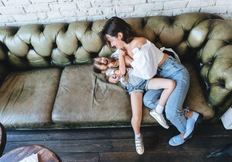 A mamã e sua menina têm o divertimento no sofá fotografia de stock royalty free