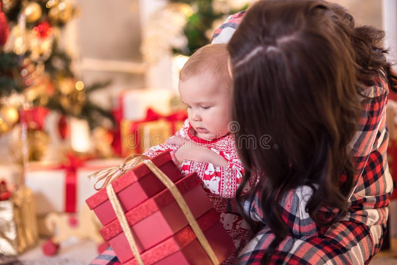 A mamã e um rapaz pequeno estão jogando perto da árvore de Natal pelo ano novo História do Natal imagem de stock royalty free