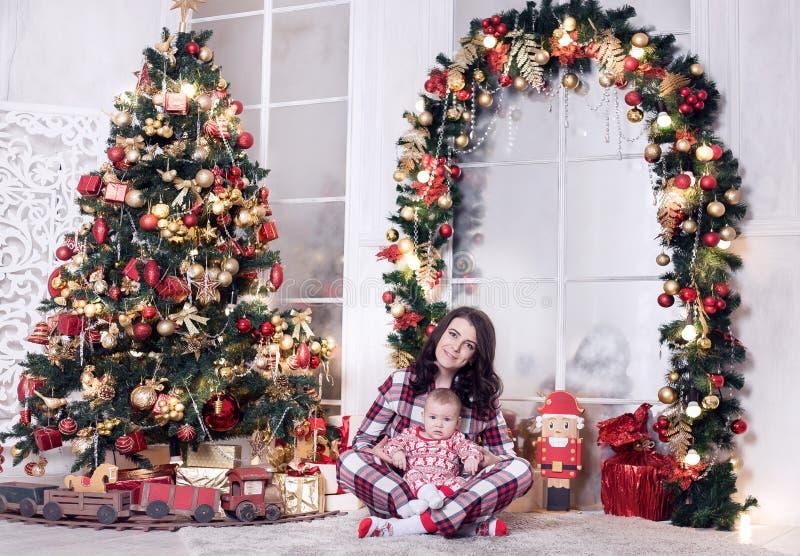 A mamã e um rapaz pequeno estão jogando perto da árvore de Natal pelo ano novo História do Natal imagem de stock