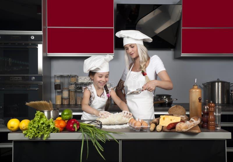 A mamã ensina a filha cozinhar fotos de stock