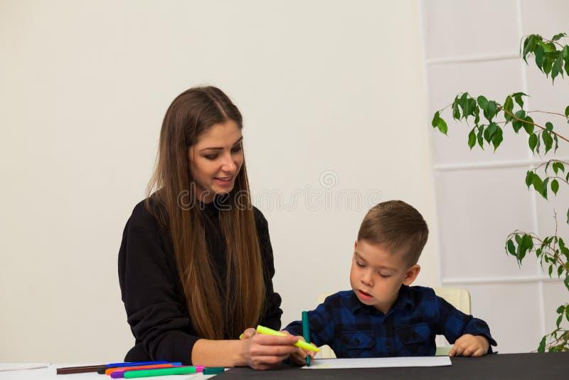 A mamã ensina o filho novo do menino tirar marcadores na tabela fotografia de stock royalty free