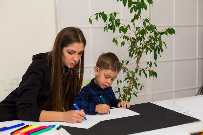 A mamã ensina o filho novo do menino tirar marcadores na tabela imagem de stock royalty free