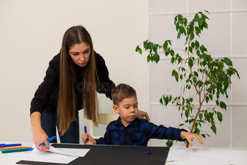 A mamã ensina o filho novo do menino tirar marcadores na tabela fotos de stock royalty free
