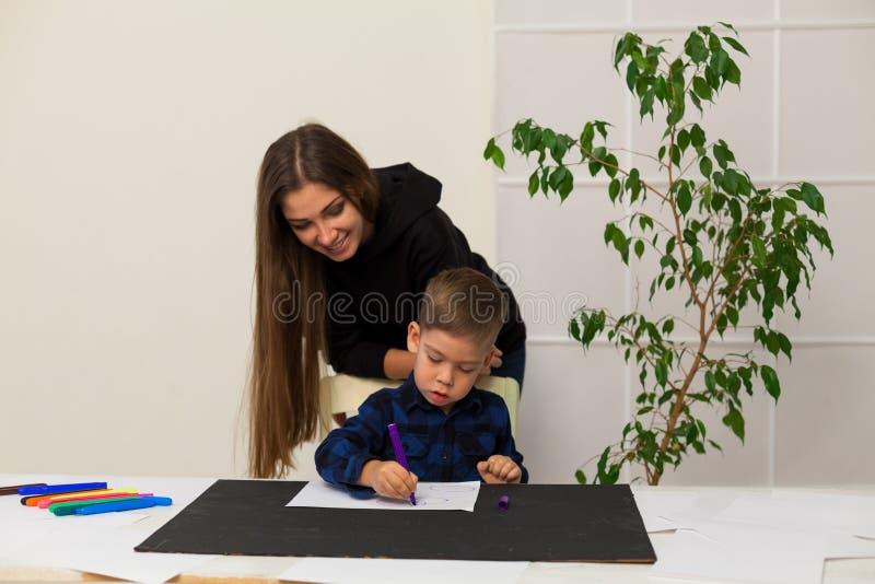 A mamã ensina o filho novo do menino tirar marcadores na tabela imagem de stock