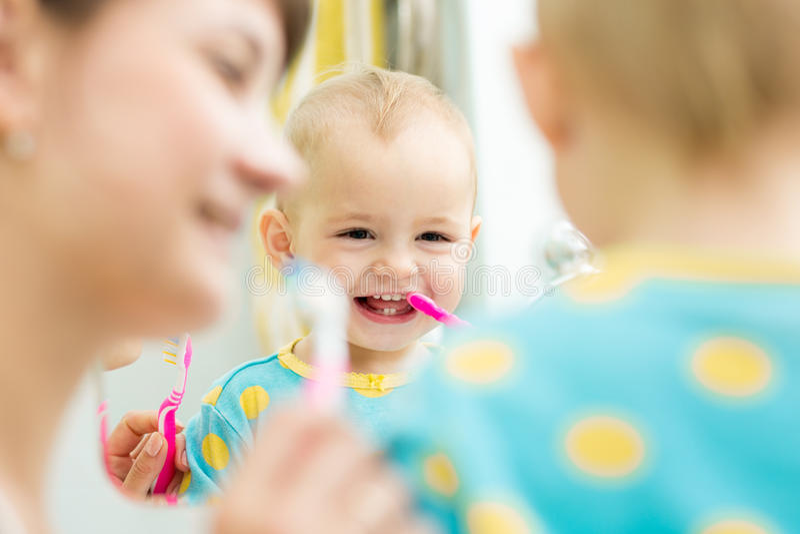 A mamã ensina os dentes de escovadela do bebê foto de stock royalty free