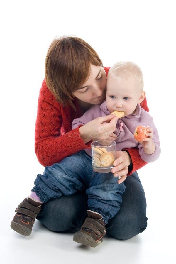 A mamã está alimentando a menina foto de stock royalty free