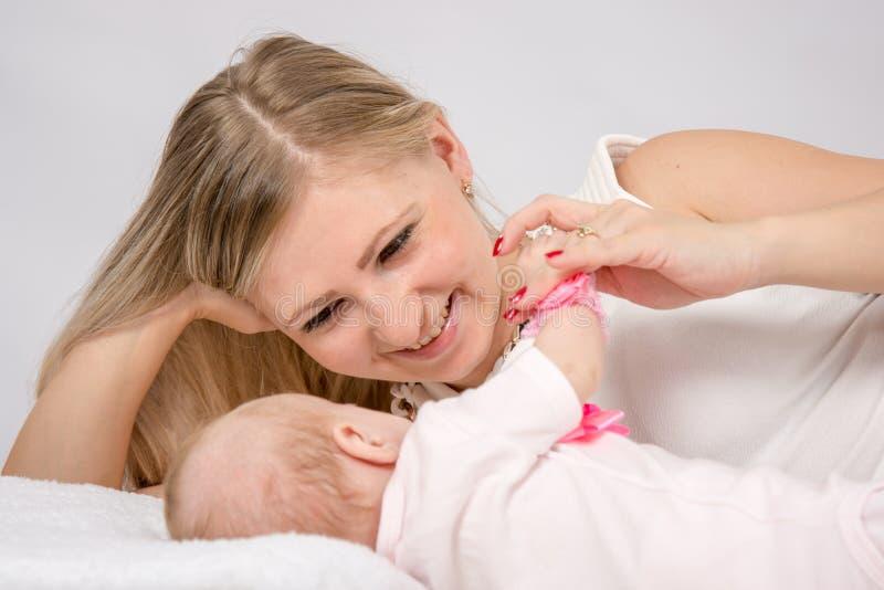 A mamã está perto de um bebê de dois meses e olha-o lovingly fotografia de stock royalty free