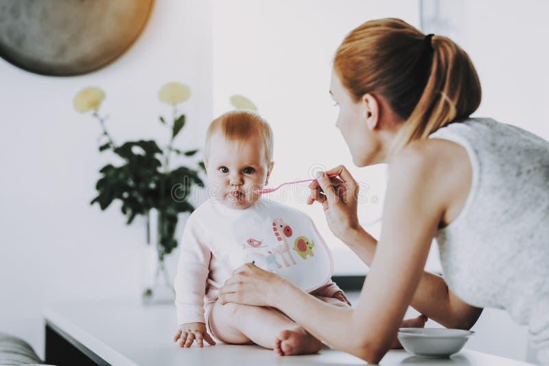 A mamã feliz alimenta o bebê adorável com colher dentro fotos de stock royalty free