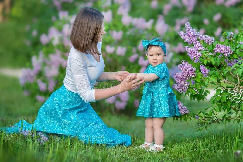 Mamã feliz da mãe com a filha que aprecia o tempo em um lugar impressionante entre o arbusto lilás da seringa Jovens senhoras com imagem de stock