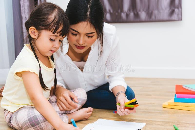 Mamã feliz da mãe da educação do professor do desenho do jardim de infância da menina da criança da criança da família com mãe bo imagem de stock
