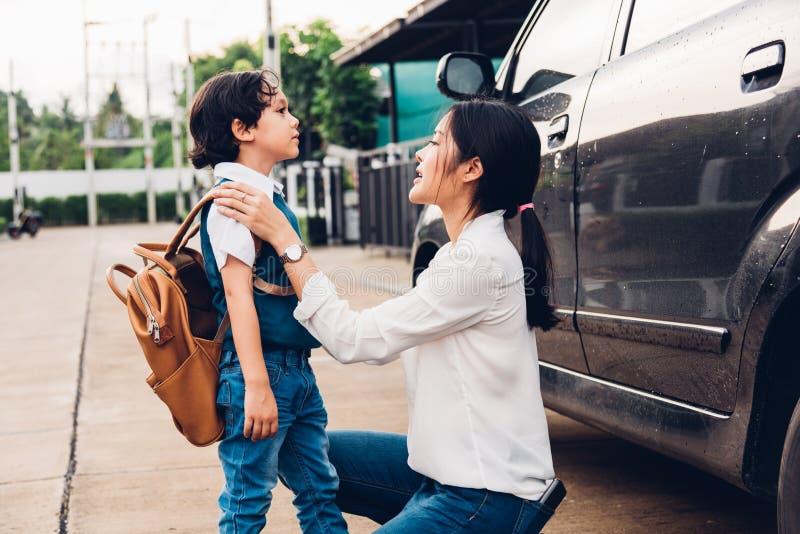 A mamã feliz da mãe da família envia crianças caçoa o jardim de infância do menino do filho à escola imagens de stock royalty free