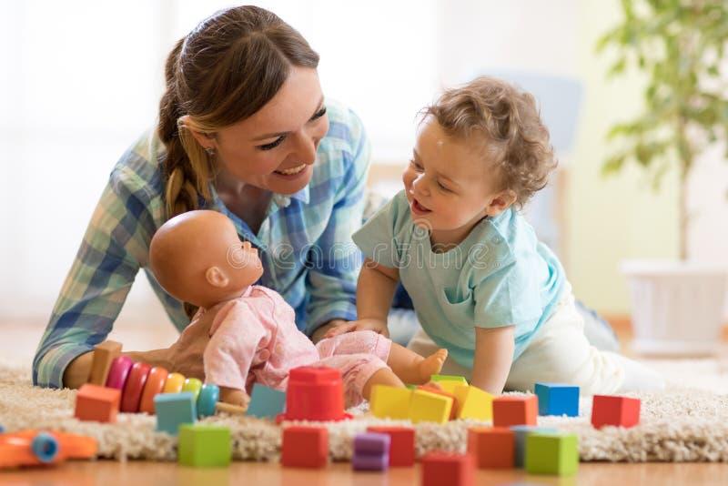 Mamã feliz que joga a boneca com o filho pequeno no assoalho fotografia de stock royalty free
