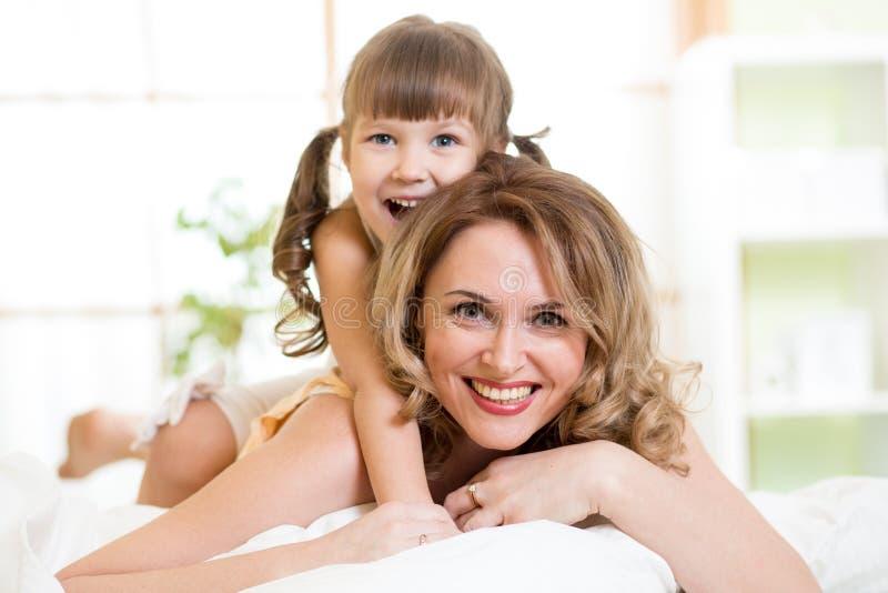 Mamã feliz que joga com sua criança na apreciação da cama fotografia de stock