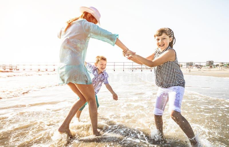 Mamã feliz que joga o whit suas crianças com o mar imagens de stock royalty free