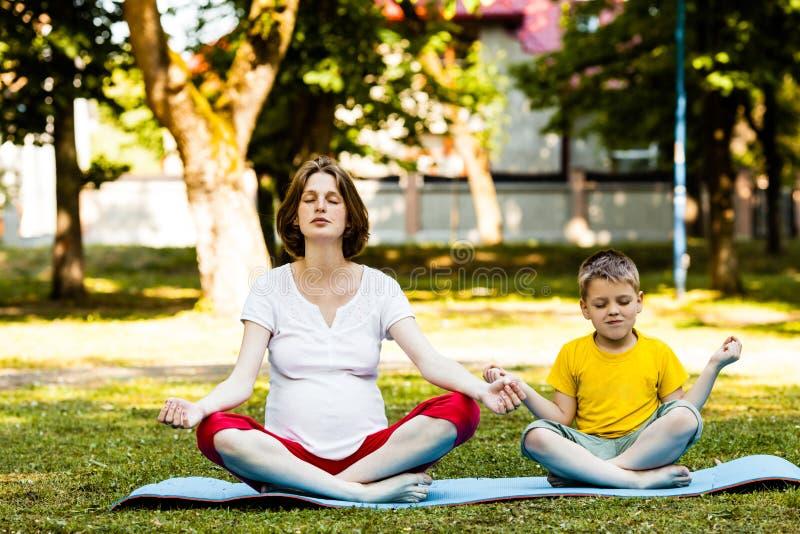 Mamã futura que relaxa quando classe da ioga exterior no verão foto de stock royalty free