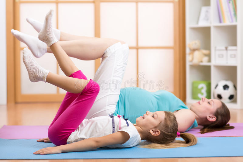 Mamã grávida com a criança que faz a ginástica e imagens de stock