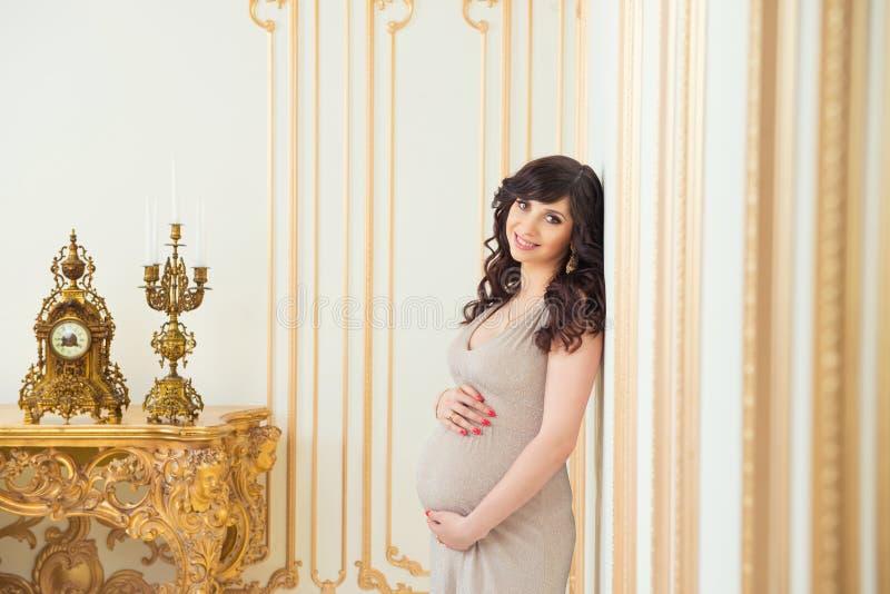 Mamã grávida elegante no vestido dourado que abraça a barriga fotografia de stock royalty free