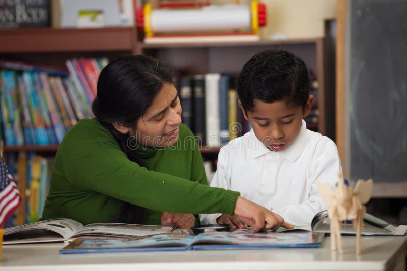 Mamã latino-americano e menino no ajuste da Casa-escola que estudam rochas fotografia de stock