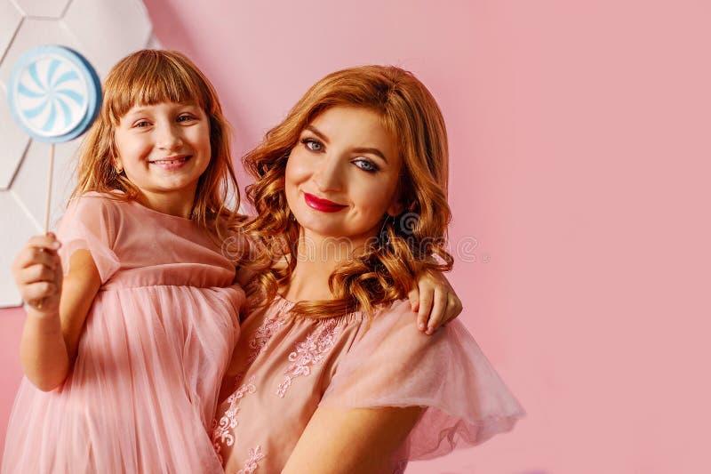 Mamã loura bonita com a filha bonito no fundo cor-de-rosa no estúdio O dia de mãe, abraços mamã da filha e sorriso felizes foto de stock