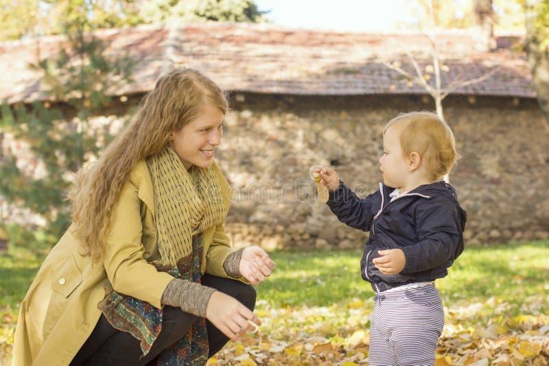 A mamã loura joga com sua filha doce no parque imagens de stock royalty free